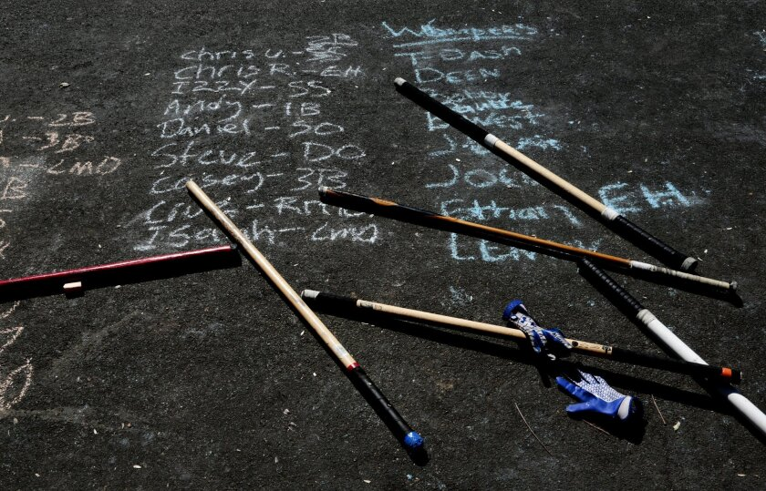 Homemade bats are piled on top of starting lineups chalked in the street during the 15th Annual San Diego Labor Day Stickball Tournament in Little Italy. The tournament uses Bronx style rules and uses a city block of street on Columbia street per game, beginning at Beech Street.