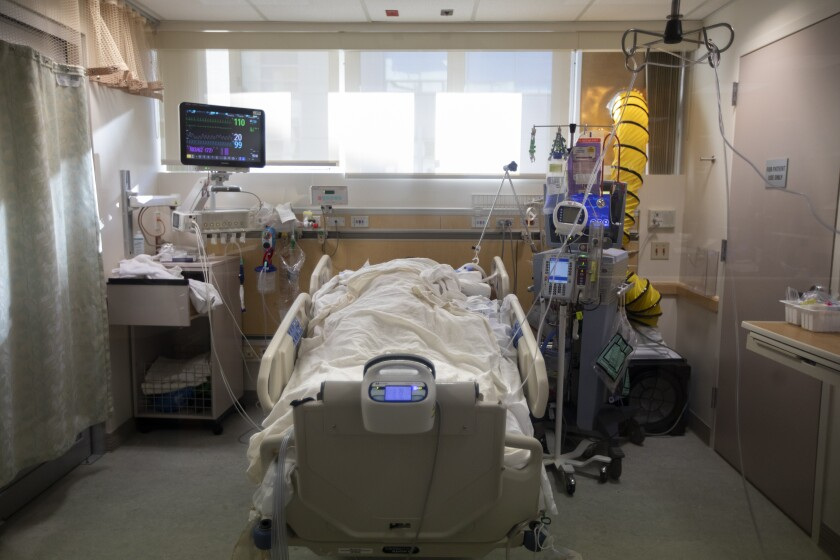 A covered patient in a hospital bed in an intensive care unit