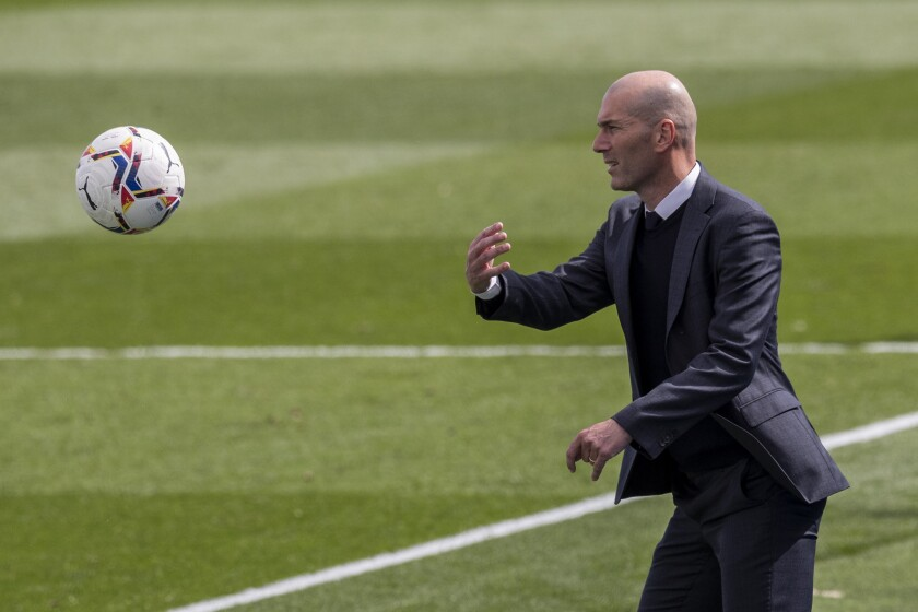 Real Madrid's head coach Zinedine Zidane throws a ball during the Spanish La Liga soccer match between Real Madrid and Eibar at the Alfredo di Stefano stadium in Madrid, Spain, Saturday, April 3, 2021. (AP Photo/Bernat Armangue)