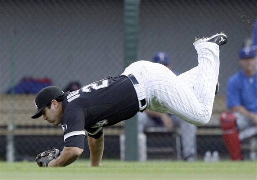 Chicago White Sox right fielder Carlos Quentin dives to make the catch a fly ball hit by Texas Rangers' Craig Gentry during the first inning of a baseball game in Chicago, on Saturday, Aug. 20, 2011. (AP Photo/Nam Y. Huh)