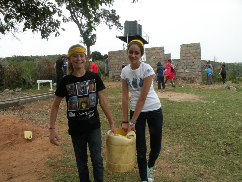 Lily Keck (left) and Rachel Church carry water to make a concrete floor.  Courtesy