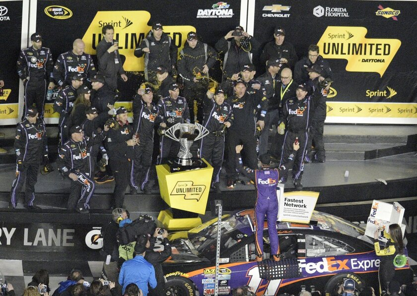 Denny Hamlin (11) celebrates with his crew, while standing on his car in Victory Lane after winning the Sprint Unlimited auto race at Daytona International Speedway, Saturday, Feb. 13, 2016, in Daytona Beach, Fla. (AP Photo/Phelan M. Ebenhack)