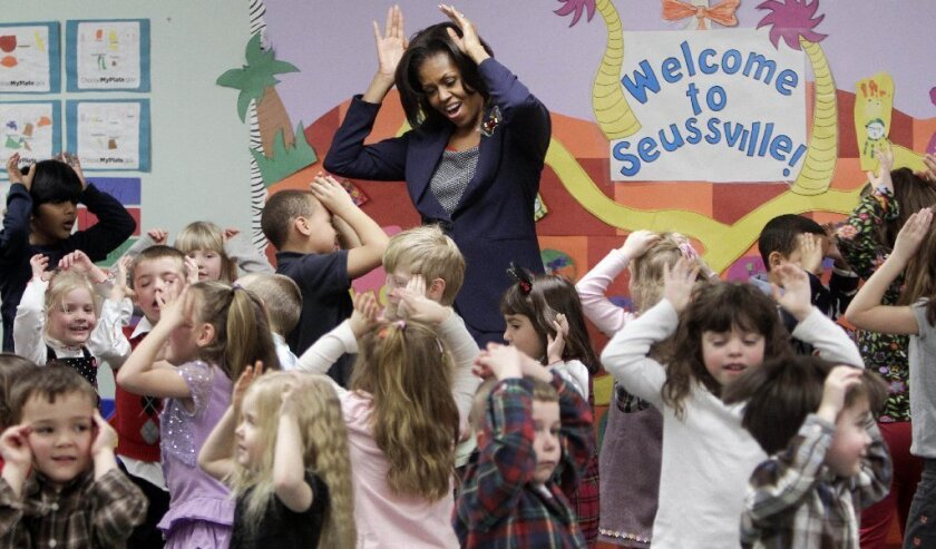 """Michelle Obama dances with children as part of her """"Let's Move"""" campaign."""
