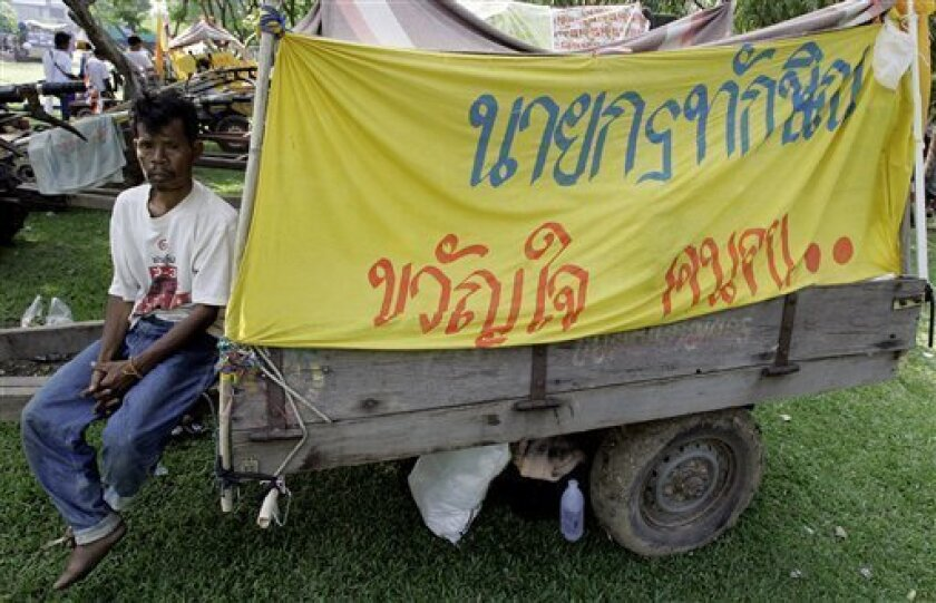 "A Thai farmer from northeastern Thailand supporter of ousted Prime Minister Thaksin Shinawatra sits on his locally assembly vehicle during a rally to support Thaksin at a park in Bangkok, Thailand, March 20, 2006. The battle to form Thailand's next government heated up Thursday, Dec. 11, 2008 as spotlight turned to Thaksin who will phone-in from exile during a rally that some fear could tip the political balance. The sign reads: ""Thaksin is hero of the poor."" (AP Photo/Apichart Weerawong)"