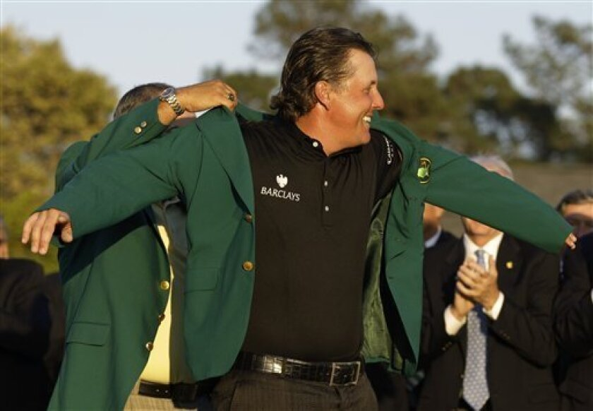 Phil Mickelson puts on the Masters jacket after winning the 2010 Masters golf tournament in Augusta, Ga., Sunday, April 11, 2010. (AP Photo/David J. Phillip)
