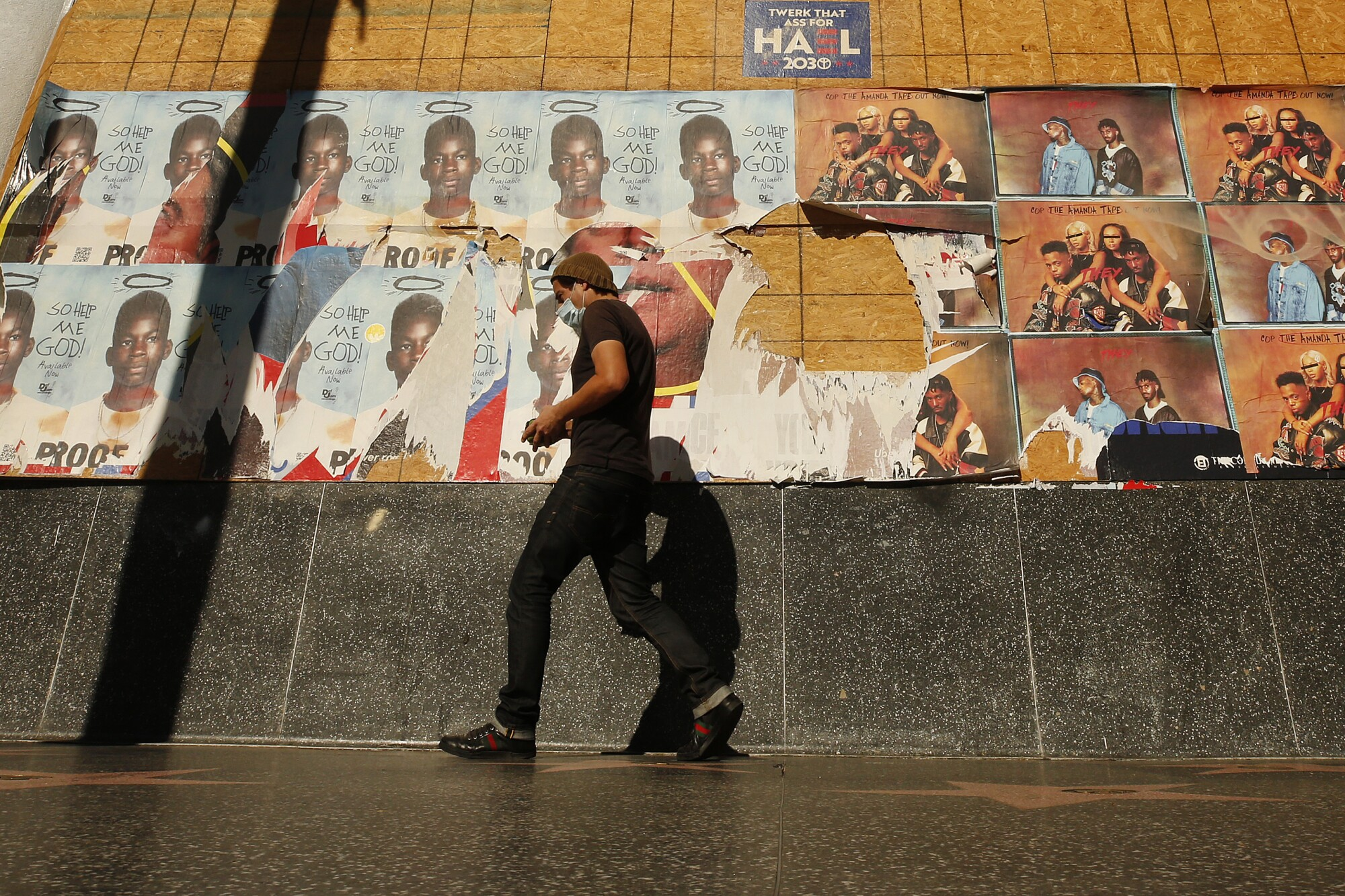 A pedestrian passes the boarded windows of a business on Hollywood Boulevard