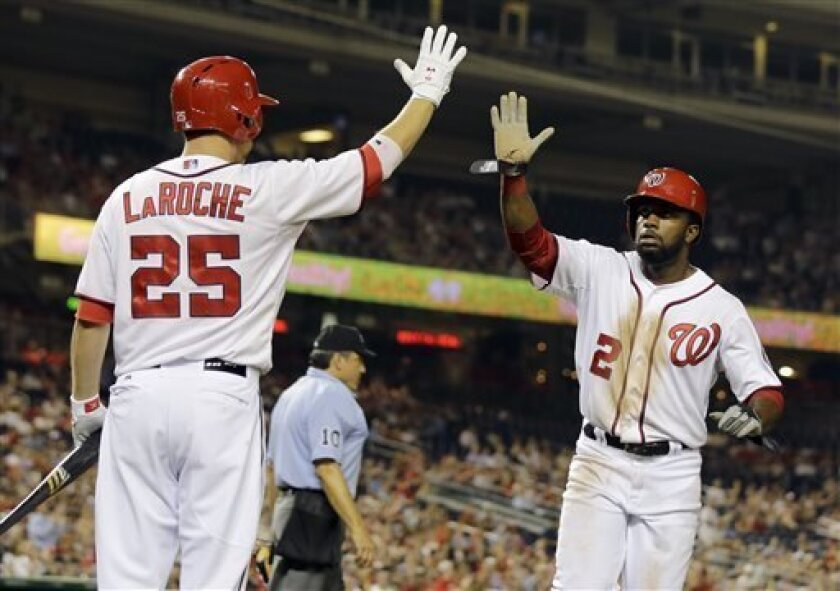 Washington Nationals' Denard Span (2) celebrates with Adam LaRoche (25), after scoring on Ryan Zimmerman's sacrifice fly during the fourth inning of an interleague baseball game against the Chicago White Sox at Nationals Park Tuesday, April 9, 2013, in Washington. (AP Photo/Alex Brandon)
