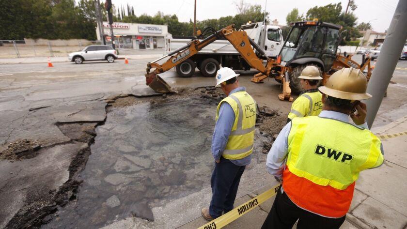 TARZANA, CA - MAY 31, 2017 - Department of Water and Power crews observe the 8 inch water main break