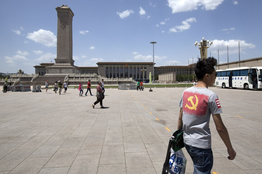 A tourist, right, wears a t-shirt displaying the logo of the Chinese Communist Party as he visits Tiananmen Square in Beijing last month.