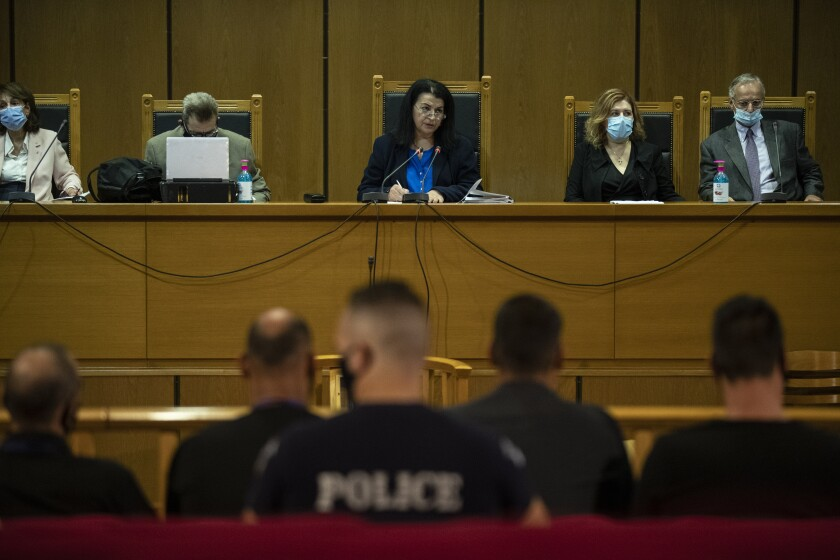 Judge Maria Lepenioti, center, delivers the verdict in a court in Athens, Wednesday, Oct. 7, 2020. The court has ruled the far-right Golden Dawn party was operating as a criminal organization, delivering landmark guilty verdicts in a politically charged five-year trial against dozens of defendants, including former lawmakers of what had become Greece's third largest party. (AP Photo/Petros Giannakouris)