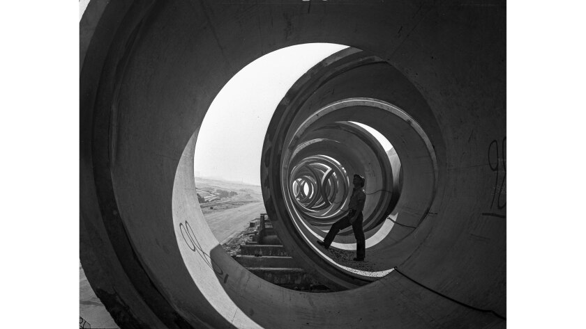 Feb. 26, 1947: A worker stands inside a concrete section of pipe being used in the construction of a new outfall sewer line. The 12-foot, 40-ton sections were sitting on the beach near Playa del Rey.