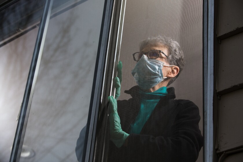 Pat McCauley stares out the window of her home in Kirkland, Wash., while she is quarantined with her husband.  The psychological toll of isolation and loneliness can be as damaging to one's health as smoking, researchers say.