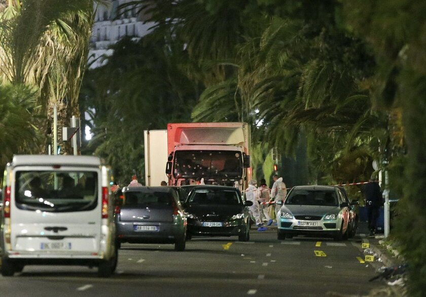 The truck which slammed into revelers late Thursday, July 14, is seen near the site of an attack in the French resort city of Nice, southern France, Friday, July 15, 2016. The truck loaded with weapons and hand grenades drove onto a sidewalk for more than a mile, plowing through Bastille Day revelers who'd gathered to watch fireworks in the French resort city of Nice late Thursday. (AP Photo/Luca Bruno)