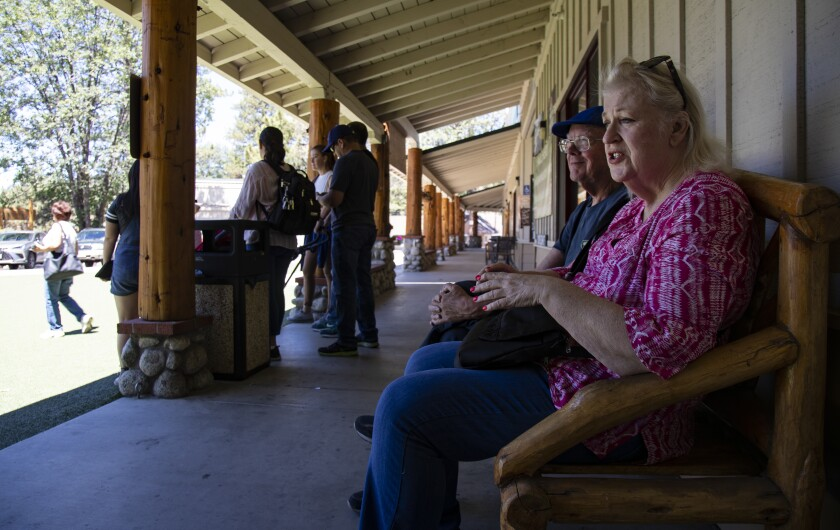 Gary Burington and Karen Bowen of San Diego sit on an Idyllwild bench,