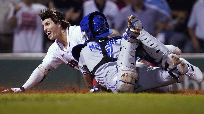 Boston Red Sox's Jarren Duran dives home to score, while advancing on an error after hitting an RBI triple, beating the tag by Toronto Blue Jays catcher Reese McGuire (7) during the fourth inning of the second baseball game of a doubleheader at Fenway Park, Wednesday, July 28, 2021, in Boston. (AP Photo/Charles Krupa)