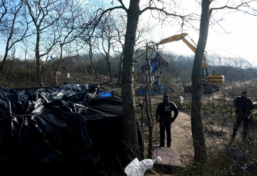 Police officers stand near a bulldozer in the Calais refugee camp, northern France Tuesday, Jan. 19, 2016. The bulldozers were used to clear a 100-meter-long strip of land between the camp and the highway. Up to 6,000 people were staying there in the fall, though the number has decreased recently. (AP Photo/Michel Spingler)