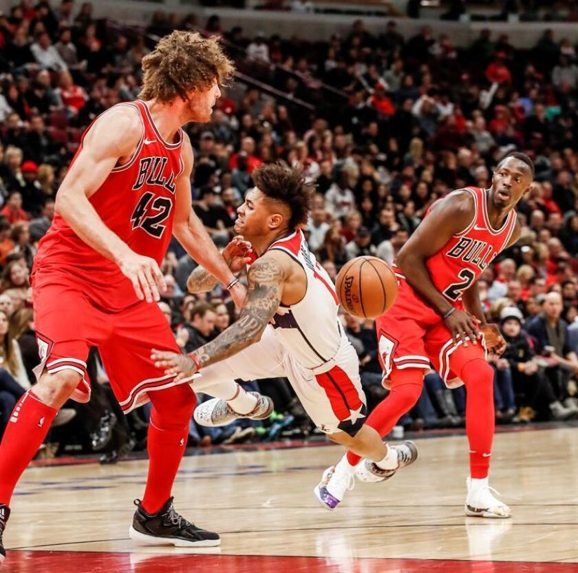 Washington Wizards forward Kelly Oubre Jr. (C) falls to the floor as he is fouled by Chicago Bulls guard Jerian Grant (R) while driving on Chicago Bulls center Robin Lopez (L) in the second half of their NBA game at the United Center in Chicago, Illinois, USA, 10 February 2018. EFE