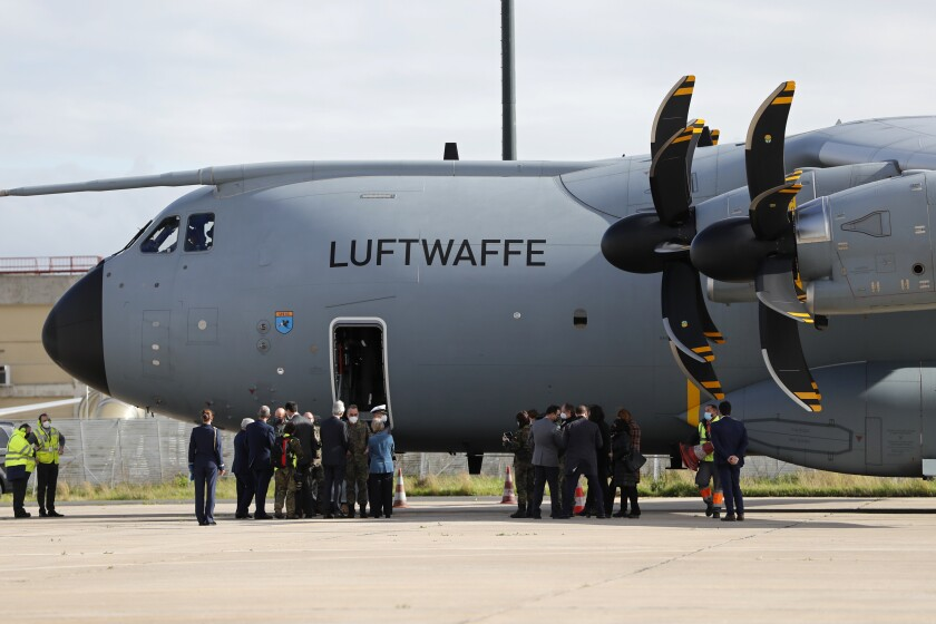 Officials greet each other next to a German air force airplane after it landed at Lisbon airport, Wednesday, Feb. 3, 2021. The airplane is bringing 26 German army medics along with medical equipment to help out at Portuguese hospitals under stress from the recent increase in COVID-19 hospitalizations. (AP Photo/Armando Franca)