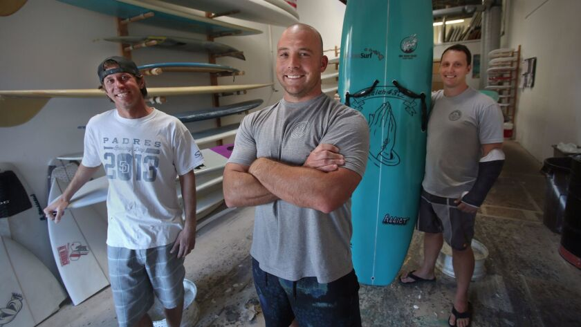 One More Wave volunteers Micah Shanahan, left, Kyle Buckett and Alex West at Shanahan's Addict Surfboards in Sorrento Valley.