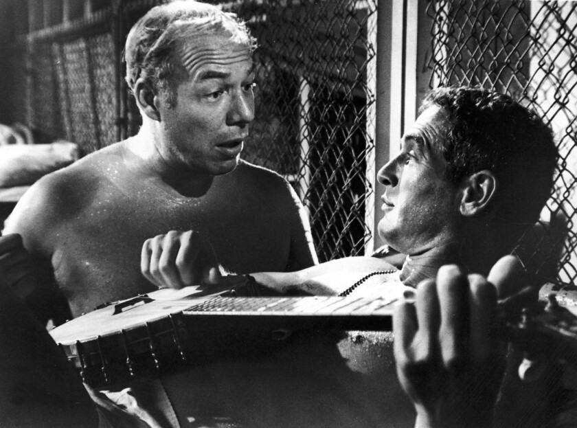 """Paul Newman, playing a banjo, and George Kennedy in the film """"Cool Hand Luke"""" directed by Stuart Rosenberg. Newman won a best actor Oscar, and Kennedy won a best supporting actor Oscar for their roles in the film."""