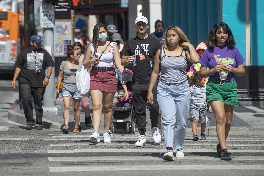 Masked and unmasked Californians crossing the street.