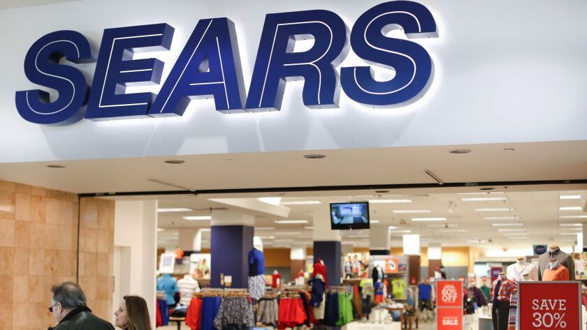 FILE - In this Wednesday, March 22, 2017, file photo, shoppers pass a Sears department store at the