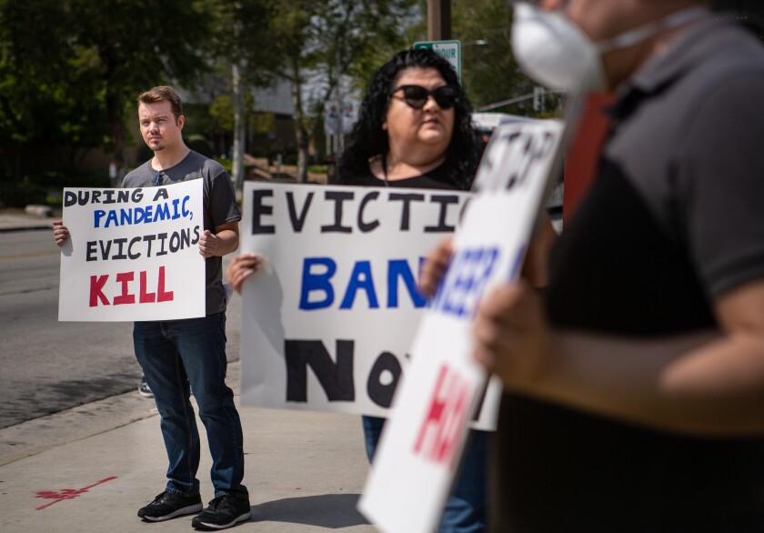 Protesters hold signs demanding an end to evictions during the pandemic.