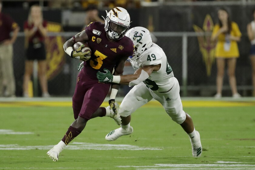 Arizona State running back Eno Benjamin (3) tries to get away from Sacramento State linebacker Armon Bailey (49) during the second half on Friday in Tempe, Ariz.