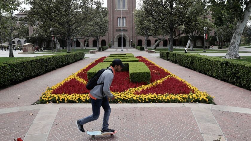 A student skateboards on the USC campus outside Bovard Hall.