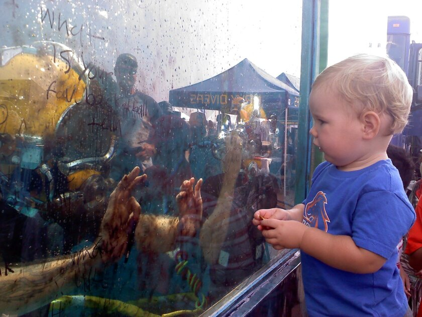 One-year-old Josiah Heinricks communicates with an underwater U.S. Navy diver at the MCAS Miramar Air Show 2010