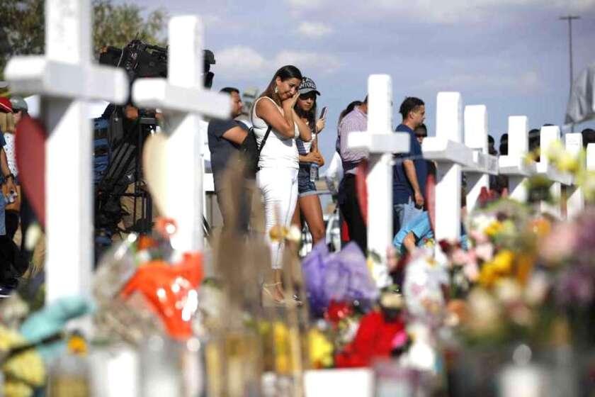 Personas visitan un altar improvisado el lunes 5 de agosto de 2019, en el lugar de una masacre en un centro comercial de El Paso, Texas.