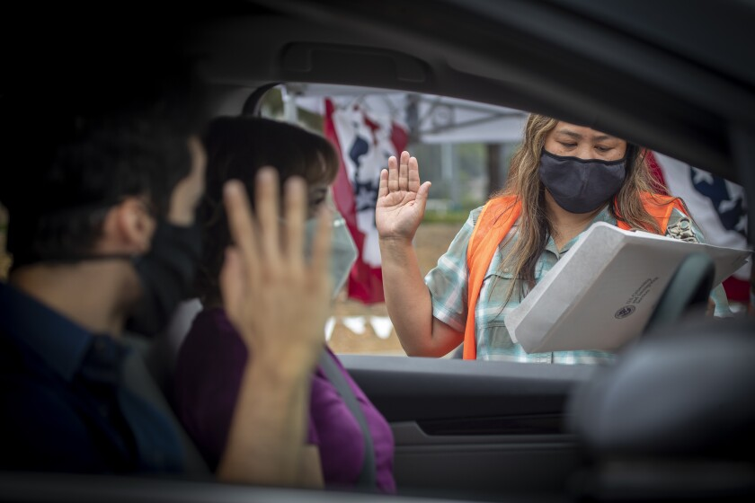 Rochelle Reyes administers oath to Brian Gebel, 26, as his mom, Liliana, listens during a drive-through ceremony.