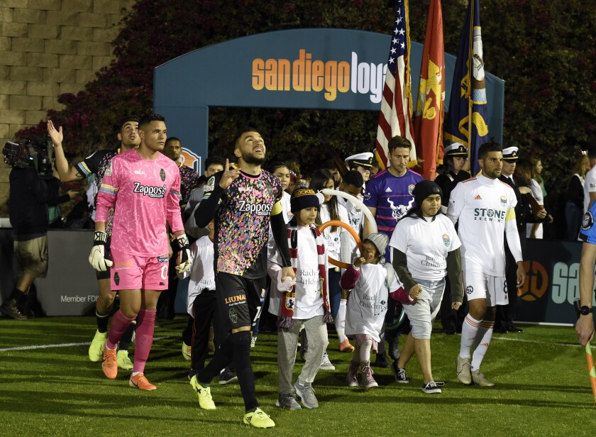 San Diego Loyal and Las Vegas Lights players come onto the field before their soccer game March 7 at USD's Torero Stadium.