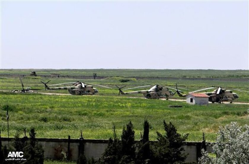 FILE - In this June 18, 2013 file photo, citizen journalism image provided by Aleppo Media Center AMC which has been authenticated based on its contents and other AP reporting, shows Syrian military helicopters at Mannagh air base in Aleppo province, Syria. Syrian rebels captured a major air base in the north of the country on Tuesday after months of fighting, depriving President Bashar Assad's forces of one of their main posts near the border with Turkey, activists said. State TV denied that th