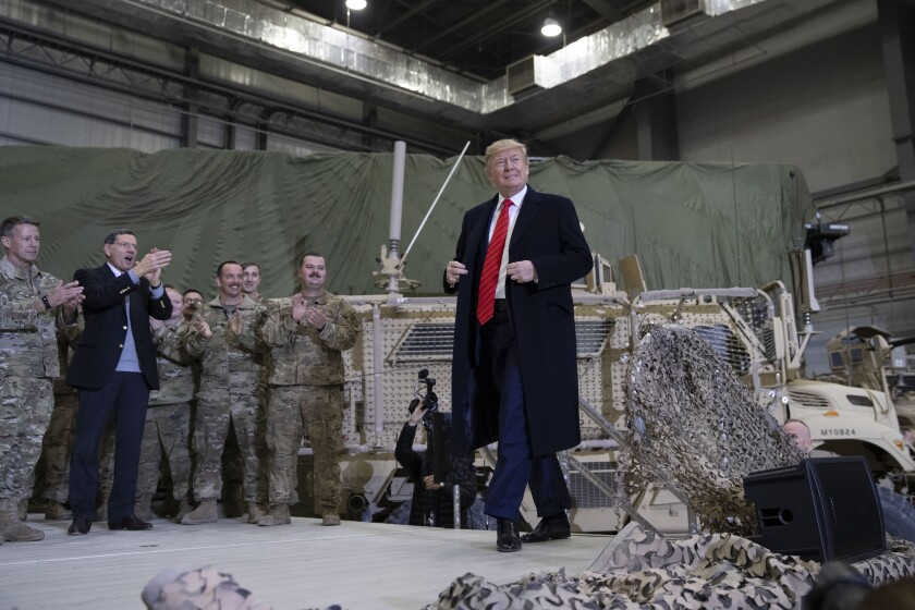 President Trump walks on stage as he arrives to speak to members of the military at Bagram Air Field, Afghanistan.