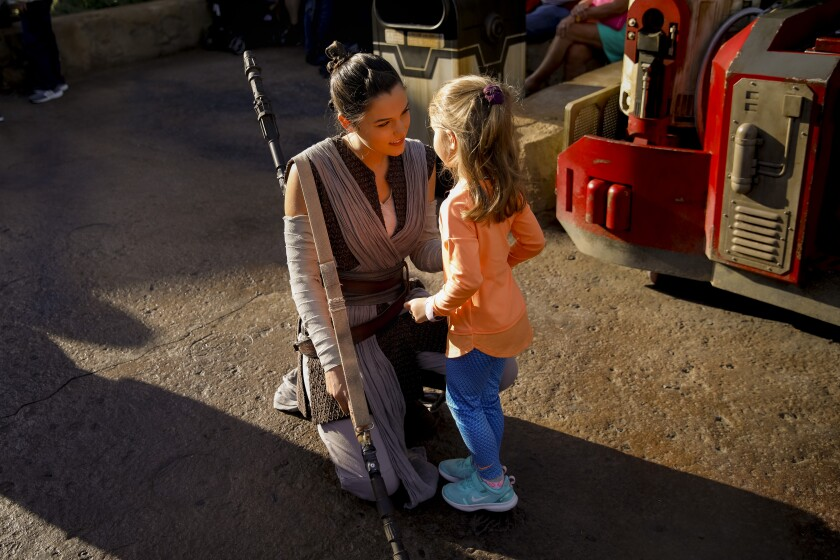 A cast member portraying Rey greets a young visitor at Star Wars: Galaxy's Edge.