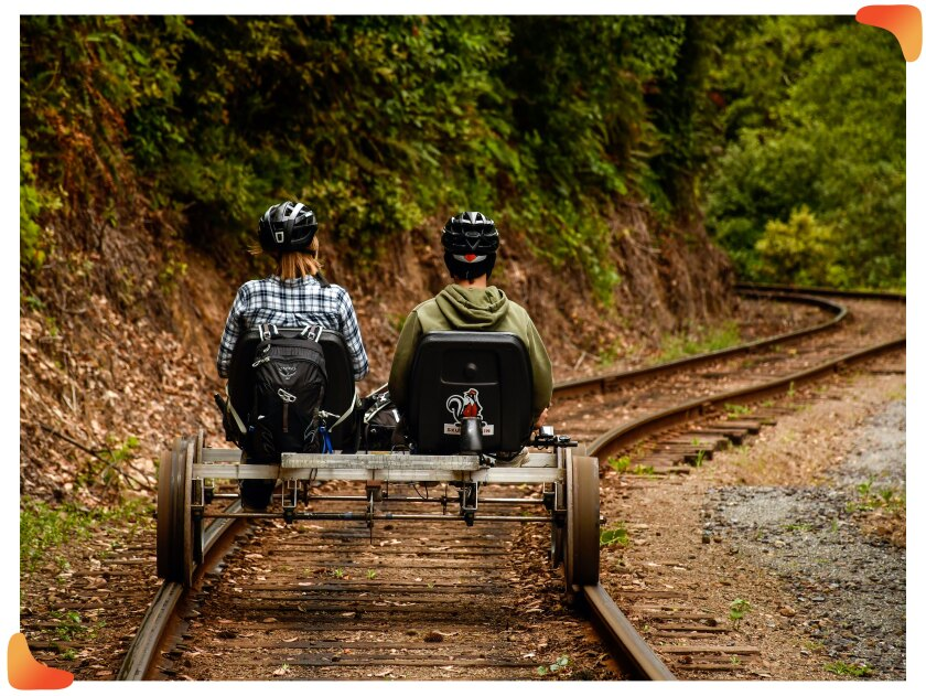 Two people pedal a railbike on tracks through a redwood forest.
