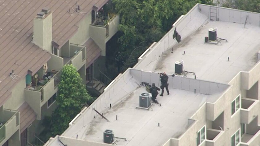 Pasadena police surround an apartment building where an armed man was barricaded Monday morning.
