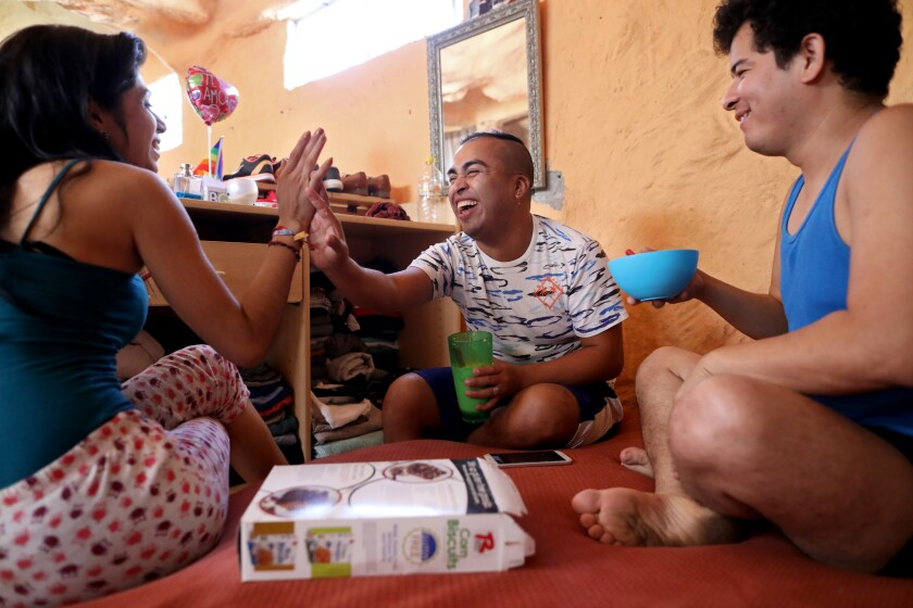 Pedro Luis Perez, 27, center, of Guatemala, with Katherine Hernandez, 24, left, of Tegucigalpa, Honduras, a transgender woman, and Perla, a 28-year-old Mexican from Guerrero, have breakfast at the Casa de Luz collective housing in Tijuana, Baja Calif., on Oct. 8, 2019. Pedro had to leave Guatemala after his dad tried to kill him and he faced multiple other assaults from police and the public. Many in the community are seeking political asylum for having received threats in their home countries for their sexual orientation.