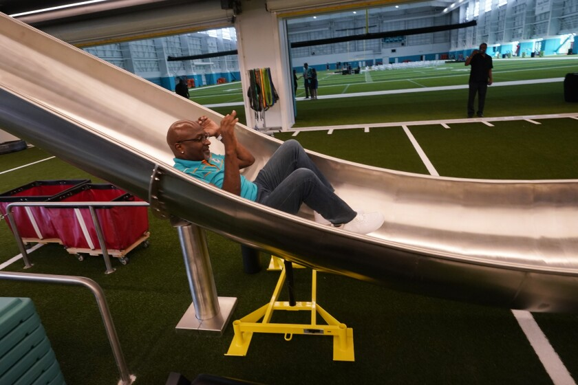 Former Miami Dolphins player O.J. McDuffie uses a slide after a ceremony at the NFL football team's new training facility, Tuesday, July 20, 2021, in Miami Gardens, Fla. The Dolphins held a grand opening for their $135 million training complex one week before the start of training camp. (AP Photo/Wilfredo Lee)