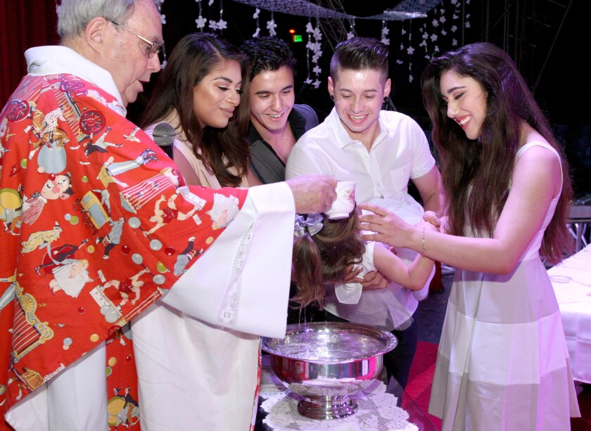 "Fr. George ""Jerry"" Hogan, baptizes Bianca Marinelli, as her mother Celeste Marinelli and godfather Patrick Marinelli, center left, look on while dad, Josue Marinelli, and godmother, Mariella Quiroga, right, hold the the baby during a Catholic mass and sacraments of initiation at Circus Vargas in Burbank on Thursday, May 19, 2016. Some members of the circus received baptism, confirmation or first communion under the circus' big top in Burbank."