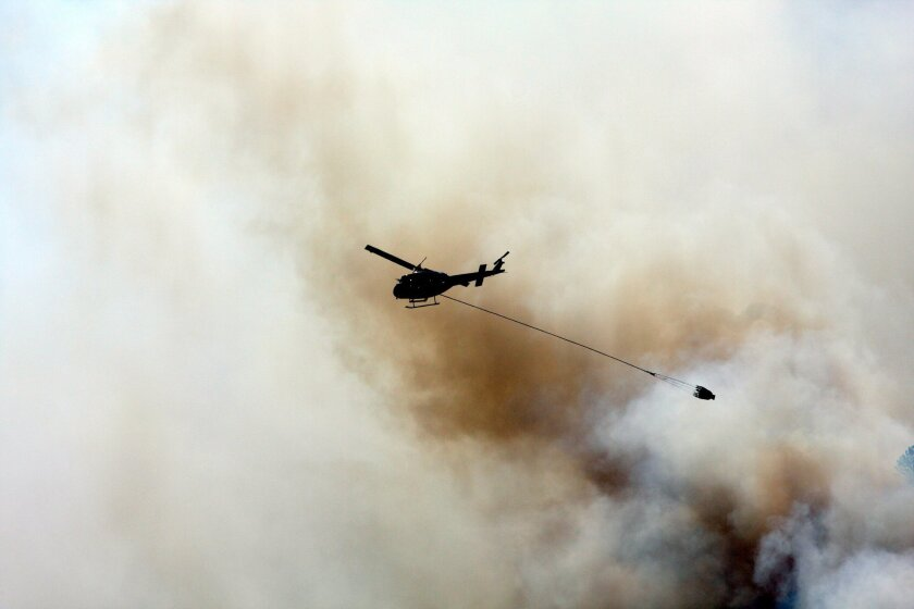 A helicopter drops water on the Rowena fire in Oregon amid high winds and dry conditions on Wednesday, Aug. 6, 2014. The Rowena fire began in brush Tuesday night. (AP Photo/The Oregonian, Stuart Tomlinson)
