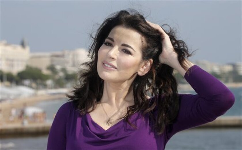 """FILE - In this Tuesday, Oct. 9, 2012 file photo, English food writer, journalist and broadcaster, Nigella Lawson poses during the 28th MIPCOM (International Film and Programme Market for TV, Video,Cable and Satellite) in Cannes, southeastern France. Celebrity chef Nigella Lawson and art collector Charles Saatchi say they intend to conclude a """"swift and amicable"""" divorce by the end of the month, with neither receiving any financial compensation from the other. The couple separated after a newspap"""