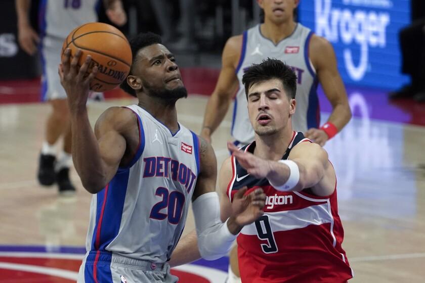 Detroit Pistons guard Josh Jackson (20) drives past Washington Wizards forward Deni Avdija (9) in the second half of a NBA basketball game in Detroit, Thursday, April 1, 2021. (AP Photo/Paul Sancya)
