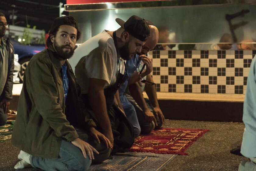 "Ramy Youssef, left, in the ""Do the Ramadan"" episode of his Hulu series ""Ramy,"" with, left to right from center, Mohammed Amer as Mo and Dave Merheje as Ahmed."