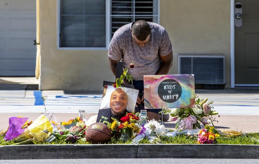 A man bows over a makeshift memorial.