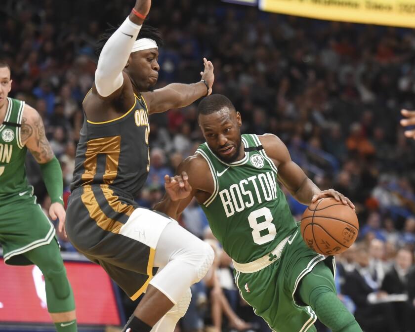 Boston Celtics guard Kemba Walker (8) drives past Oklahoma City Thunder guard Luguentz Dort (5) in the second half of an NBA basketball game, Sunday, Feb. 9, 2020, in Oklahoma City. (AP Photo/Kyle Phillips)