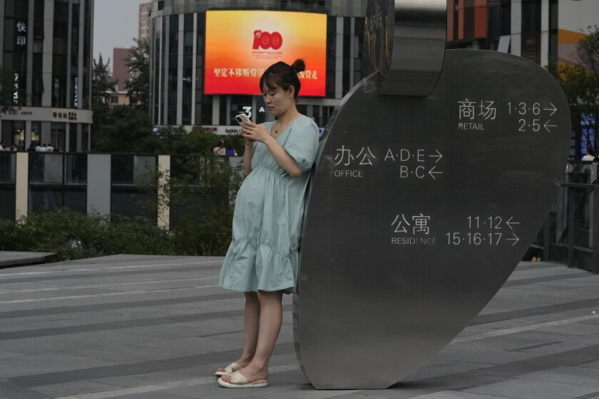 A pregnant woman looks at her smartphone near a logo marking the 100th anniversary of the founding of the ruling Communist Party in Beijing on Thursday, July 8, 2021. China's government tried Thursday to quell investor fears about tighter controls on internet companies that caused share prices to plunge, saying Beijing supports their growth. (AP Photo/Ng Han Guan)