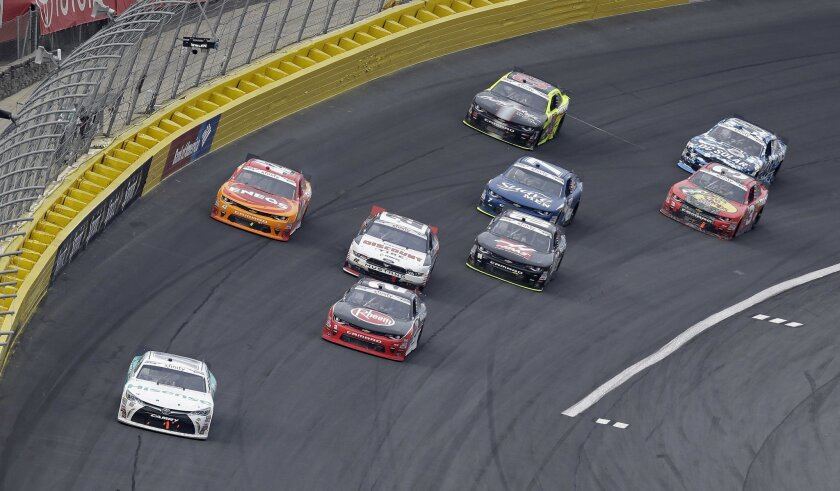 Denny Hamlin, left, leads the field out of Turn 4 on the closing lap during the NASCAR Xfinity Series auto race at the Charlotte Motor Speedway in Concord, N.C., Saturday, May 28, 2016. Hamlin won the race. (AP Photo/Gerry Broome)