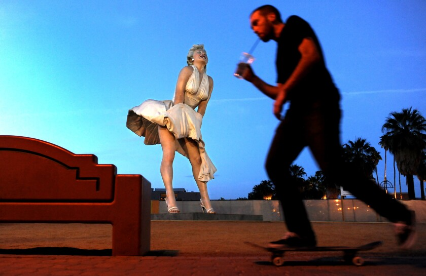 A skateboarder rides past a 26-foot statue of Marilyn Monroe in Palm Springs. The statue will be moved to New Jersey but residents hope to keep the art piece in the desert town.